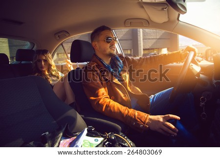 fashionable male driven in the backseat a stunning girl. Inside photo - stock photo
