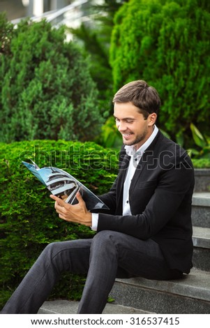 Fashionable man is sitting on stairs and reading a journal of luxury life. He is wearing a dress code like a rich man and smiling. He enjoys his life