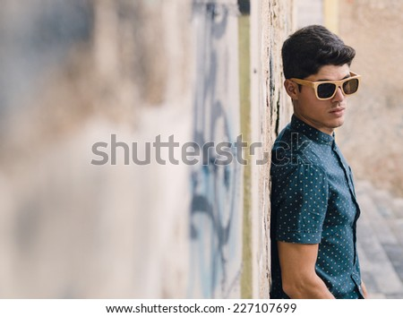 Fashionable man portrait over ruinous wall background outdoors