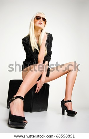 fashionable model sitting on the cube. Studio shot - stock photo