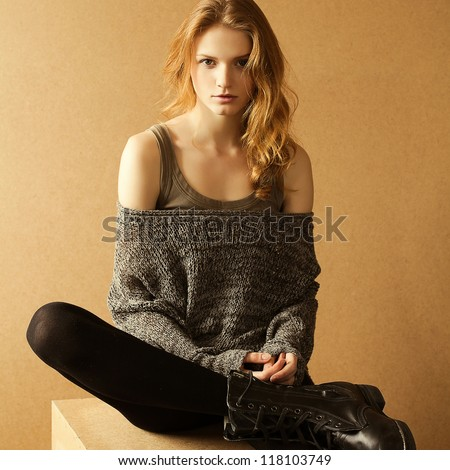 fashionable model with curly ginger hair sitting on a wooden cube over the wooden background. daylight. studio shot
