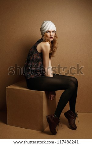 fashionable model with curly red hair and white hat sitting on cube over wooden background. studio shot