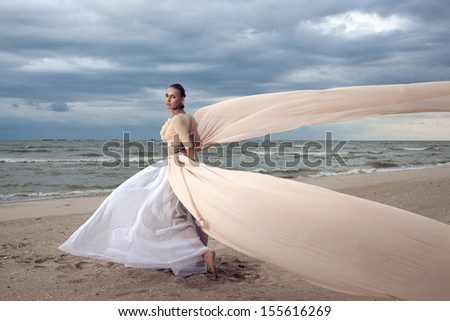 Fashionable model with extremely long dress like a wings. Vogue style. Beautiful model walks at the beach - stock photo