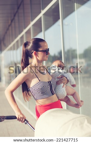 Fashionable mother and baby in arms - stock photo