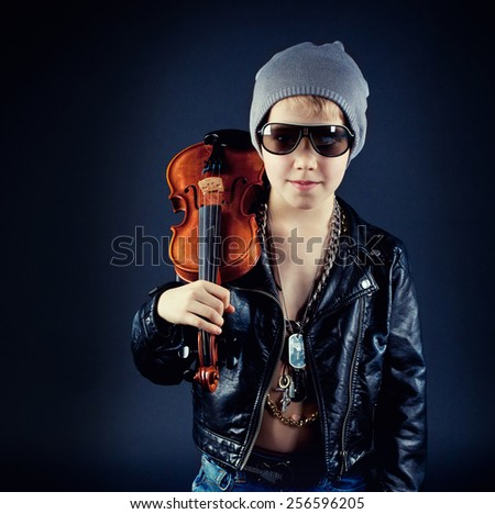 Fashionable musician posing with his Instrument on dark background - stock photo