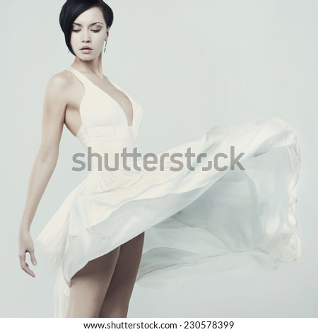 Fashionable photo of beautiful young lady in a billowing white dress - stock photo