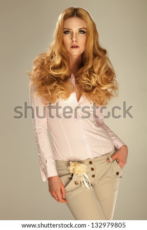 Fashionable photo of young beautiful blonde woman posing. Long curly hair. - stock photo