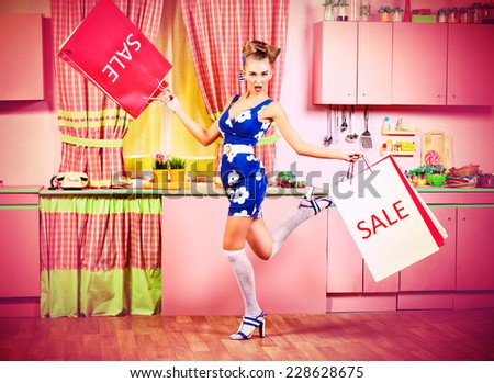 Fashionable pin-up girl standing with shopping bags on a pink kitchen. Retro style. Sale. - stock photo