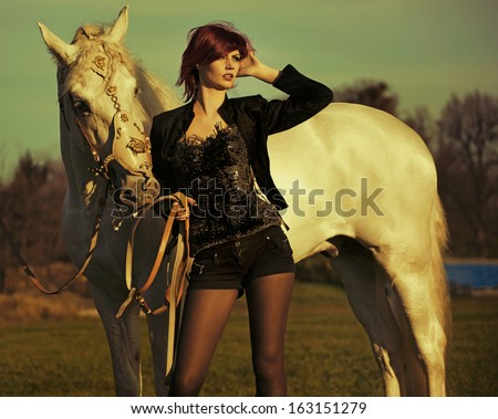 Fashionable portrait of a beautiful young woman and horse - stock photo