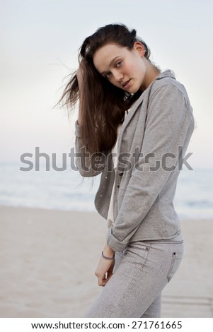 Fashionable portrait of a girl posing on the beach at sunset in a stylish comfortable clothing. Young woman outdoors