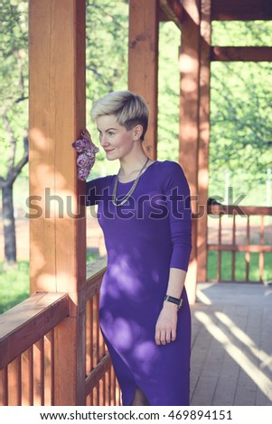 Fashionable portrait of a young beautiful woman in purple sexy evening dress and sneakers. Trendy blonde hipster girl having fun on a terrace of a rich wooden house on a sunny day.