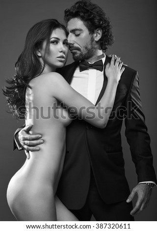 Fashionable portrait of elegant sexy couple in studio. Brutal man in suit hugging a naked woman on dark background. Grayscale - stock photo