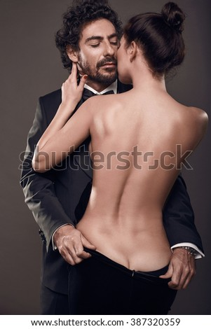 Fashionable portrait of elegant sexy couple in studio. Brutal man in suit touching a naked woman's back in dress on dark background