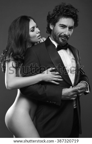 Fashionable portrait of elegant sexy couple in studio. Naked beautiful woman touching a brutal man in suit on on dark background. Grayscale - stock photo