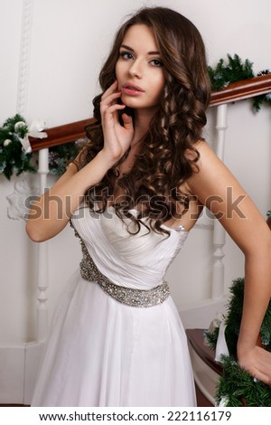 Fashionable portrait of young beautiful girl with dark curly hair posing against christmas tree in bright interior on New Year eve - stock photo