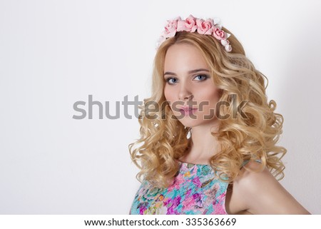 Fashionable portrait shot of a beautiful sexy girl in a cute blonde with curly hair wearing a wreath of flowers handmade in the evening image on a white background in studio - stock photo