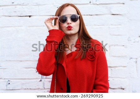 fashionable portrait young pretty redhead woman outdoor . Beautiful girl in stylish sunglasses blowing a kisses - stock photo