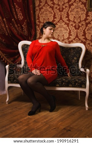 Fashionable pregnant female posing in a luxury interior
