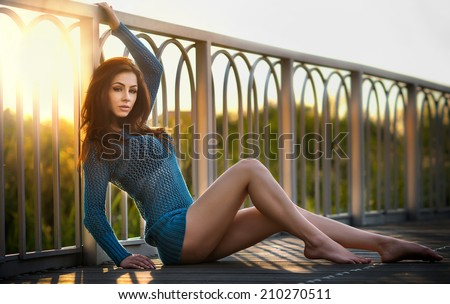 Fashionable redhead in blue blouse and long legs laying down on a wooden bridge. Beautiful girl with long hair posing, outdoor shot. Attractive young woman in bright blue having resting during sunset. - stock photo