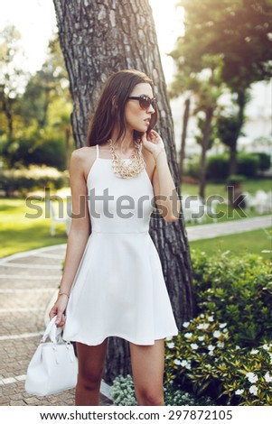Fashionable rich woman posing in park - stock photo