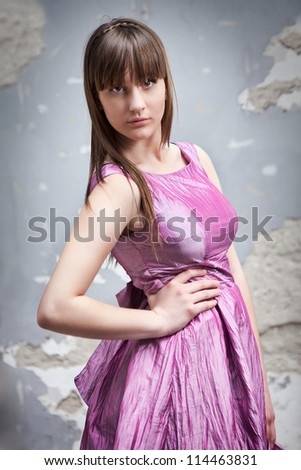 Fashionable romantic girl in pink dress over grunge wall