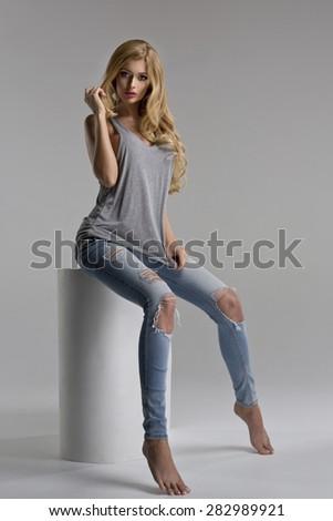 Fashionable sexy blonde woman posing in studio, looking at camera - stock photo