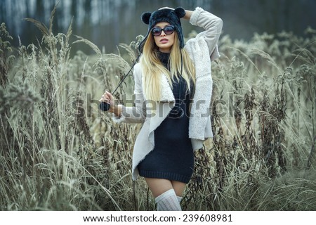 Fashionable sexy blonde woman posing outdoor. Girl wearing fur and sunglasses. - stock photo