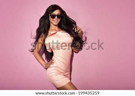 Fashionable sexy brunette woman posing over pink background in studio, smiling, looking at camera. - stock photo