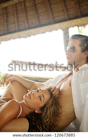 Fashionable sexy young couple lounging on an outdoors tropical bed in an exotic hotel spa garden, relaxing together and looking cool. - stock photo