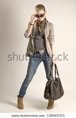 Fashionable shopping girl. Sexy blond Caucasian female in sunglasses holding leather bag. - stock photo