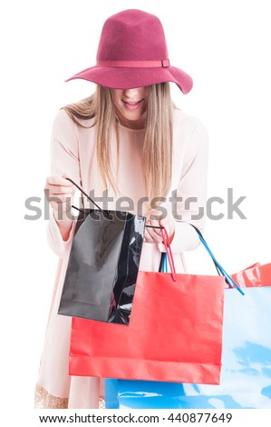 Fashionable smiling caucasian woman looking inside black gift bag with copyspace isolated on white background - stock photo