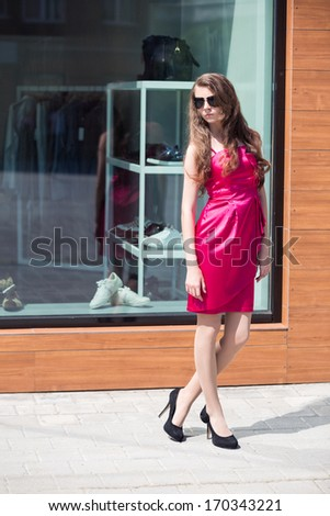 Fashionable smiling young girl in red dress outdoor