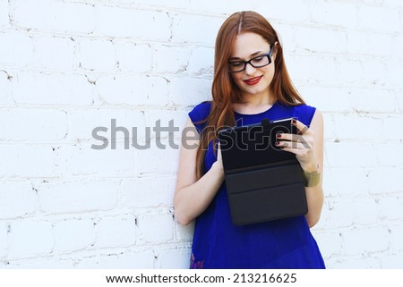 fashionable smiling young woman using a tablet  white background outdoor - stock photo