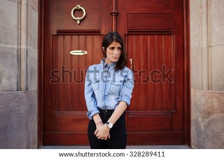 Fashionable street-style photo session with lovely lady, young girl posing outdoors,  Trendy look of amazing female model on the background of ancient door. Young hipster women wearing stylish clothes - stock photo