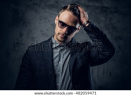 Fashionable studio portrait of male in a suit and sunglasses on grey background.