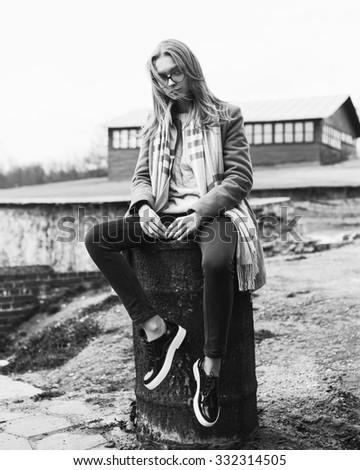 Fashionable stylish beautiful girl in sunglasses sitting on a barrel - stock photo