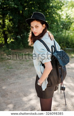 Fashionable stylish beautiful girl in the summer park with a backpack in a hat. Stylish brunette