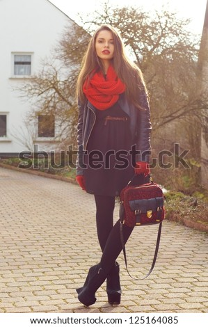 fashionable stylish girl in black dress and leather jacket with red bag - stock photo