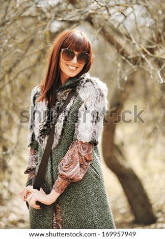 Fashionable stylish woman in casual dress wearing sunglasses with handbag - stock photo
