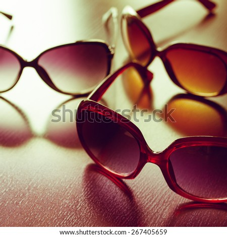 Fashionable sunglasses, focus on foreground. Vintage stylized. - stock photo