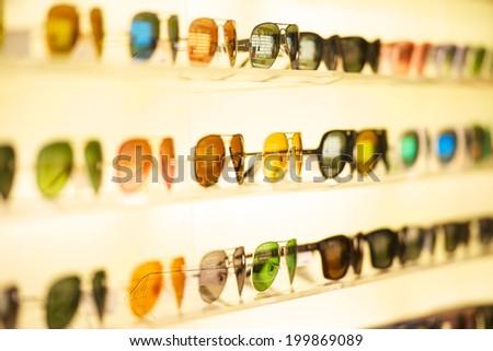 fashionable sunglasses on the shop shelf - stock photo