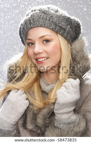 Fashionable Teenage Girl Wearing Cap And Fur Coat In Studio With Snow - stock photo
