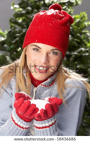 Fashionable Teenage Girl Wearing Cap And Knitwear Holding Snowball In Studio In Front Of Christmas Tree - stock photo