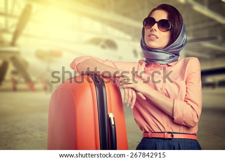 Fashionable woman at the airport on the plane background - stock photo