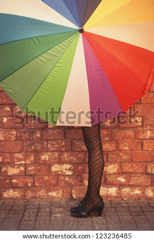 Fashionable woman hides behind an umbrella - stock photo