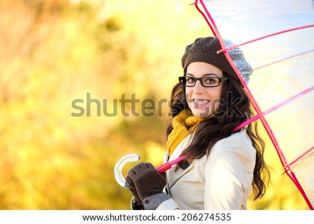 Fashionable woman holding umbrella on rainy cold autumn day. Fashion brunette wearing glasses and warm clothes on yellow autumnal background. - stock photo