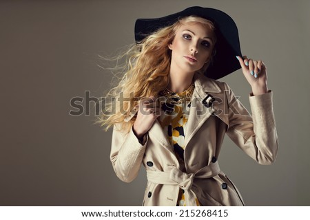 Fashionable woman in a hat and coat,  posing in studio - stock photo