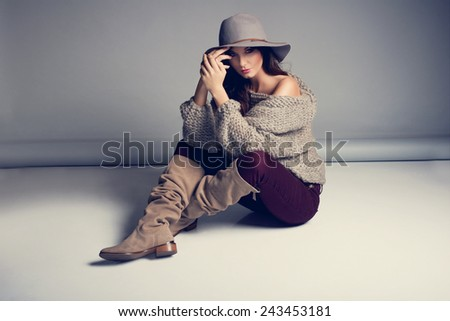 Fashionable woman in a hat, boots and autumn clothes, posing in studio. Long sweater  - stock photo