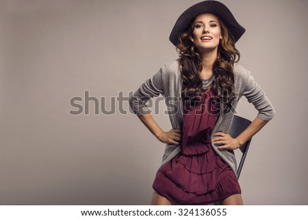 Fashionable woman in a hat, dress and long grey sweater, posing in studio. Fashion autumn photo - stock photo