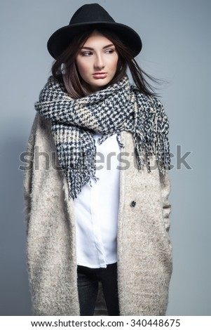 Fashionable woman in coat, woolen scarf and hat posing in studio over grey background. - stock photo